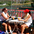 Two women enjoying a cold drink after a game of tennis in the su — Stock Photo