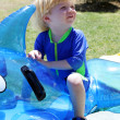 Young boy or child sitting on inflatable dolphin by swimming poo — Stock Photo