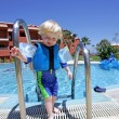 Young boy climbing out of swimming pool on vacation — Stock Photo