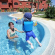 Stock Photo: Mother helping her young son to swim and jump in sunny swimmin
