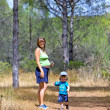 Young mother and son walking through woods — Stock Photo
