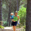 Young mother carrying her son and walking through woods — Stock Photo