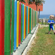 Young boy walking beside colourful fence in the summer — Stock Photo #6233924