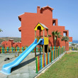 Colourful fence and childrens playground in Spanish vacation apa - Stock Photo