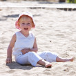 Stock Photo: Young child sitting on beach with pink hat