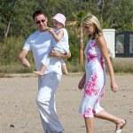 Young, healthy family walking along a sunny beach — Stock Photo #6233965
