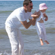 Man lifting his daughter and playing in the sea — Stock Photo