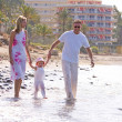 Stock Photo: Young, healthy family walking along sunny beach