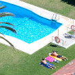 Aerial view of sunbathing by a swimming pool — Stock Photo #6234190