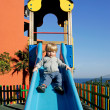 Young boy or toddler coming down a slide in the sun — Stock Photo #6234606