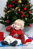 Young boy or toddler talking on mobile phone under a christmas t — Stock Photo