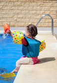 Girl toddler sitting next to swimming pool — Foto Stock