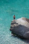 Aerial photo of young boy on rock looking into sea — Stock Photo