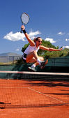 Girl jumping tennis net — Stock Photo