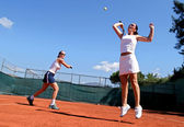 Two female tennis players playing doubles in the sun. One is lea — Stock Photo