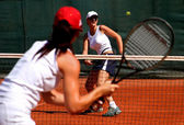 Two young sporty female tennis players having a game in the sun. — Stock Photo