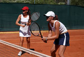 Two fit, young, healthy women playing doubles at tennis in the s — Stock Photo
