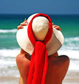 Girl sitting on sandy beach in the sun adjusting hat. Blue sky, — Stock Photo