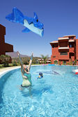 žena házet hračky nafukovací delfínů ve vzduchu — Stock fotografie