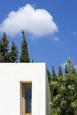 Nová, bílá budova s stromy a modrá obloha — Stock fotografie