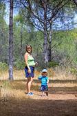 Joven madre y su hijo caminando por el bosque — Foto de Stock