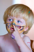 Young boy covered in face paint — Stock Photo