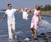 Young family playing with daughter on beach in Spain — Stock Photo