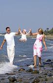 Joven familia jugando con la hija en la playa en españa — Foto de Stock
