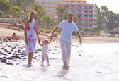 Young, healthy family walking along a sunny beach — Stock Photo