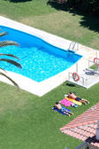 Aerial view of sunbathing by a swimming pool — Stock Photo