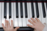 Young boys hands playing piano or keyboard — Stock Photo