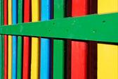 Linhas coloridas de madeira pintada em uma cerca de parque infantil — Foto Stock