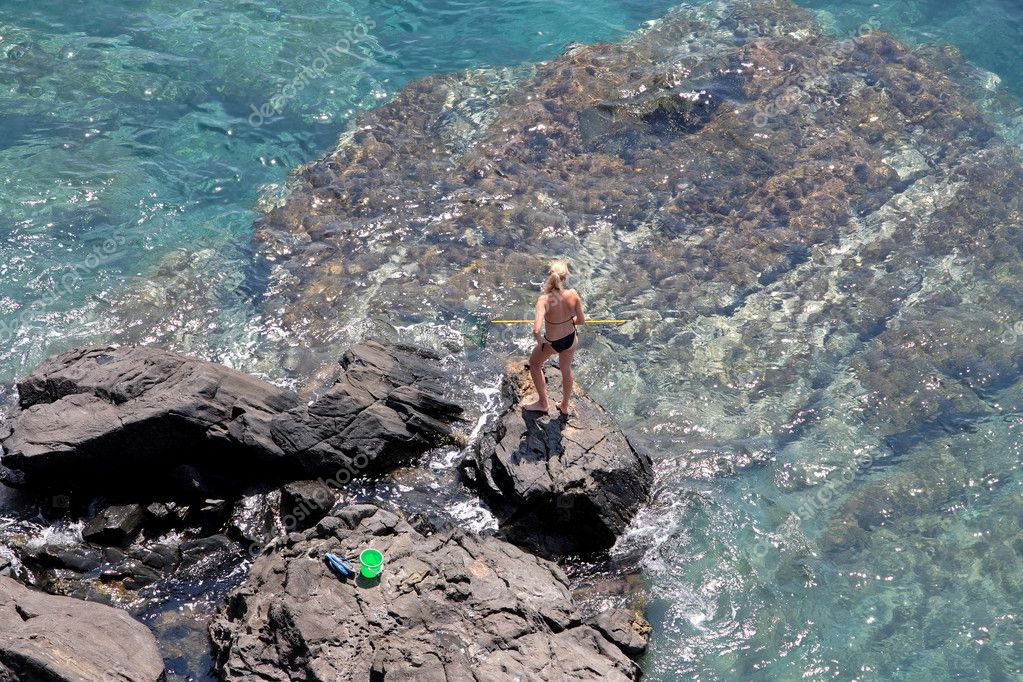 Aerial view of young woman fishing on sunny rocks on Mediterranean Ocean with net — Stock Photo #6232022