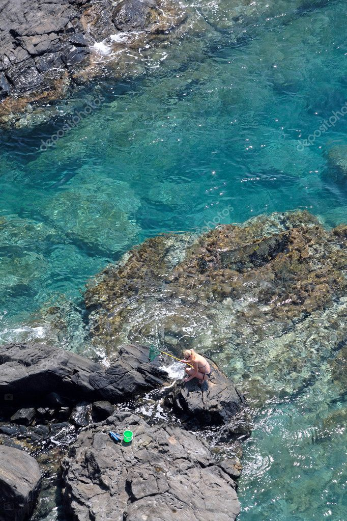 Aerial view of young woman fishing on sunny rocks on Mediterranean Ocean with net — Stock Photo #6232031