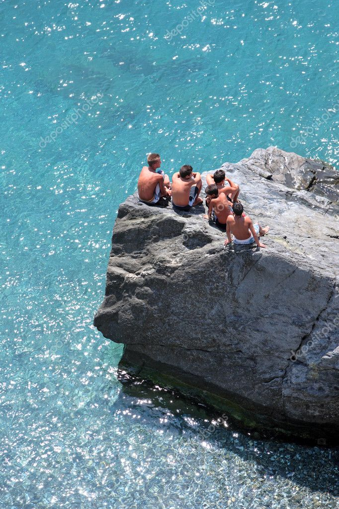 Five young boys sitting on some rocks watching the day go by on the Mediterranean Sea in Spain — Foto Stock #6232105