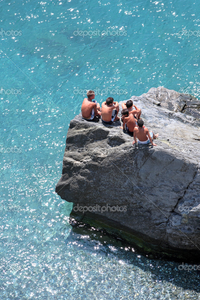 Five young boys sitting on some rocks watching the day go by on the Mediterranean Sea in Spain — Lizenzfreies Foto #6232105