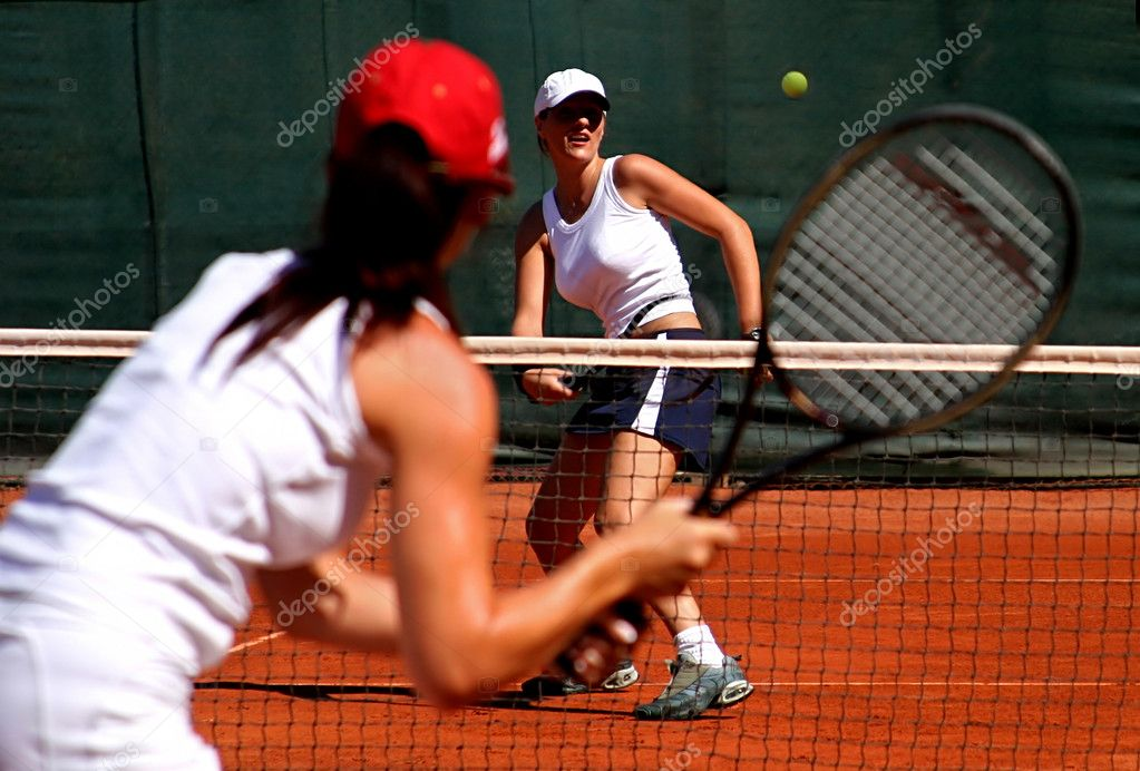 Two young, fit and tanned sporty female tennis players having a game in the sun on red asphalt court.  Stock Photo #6232707