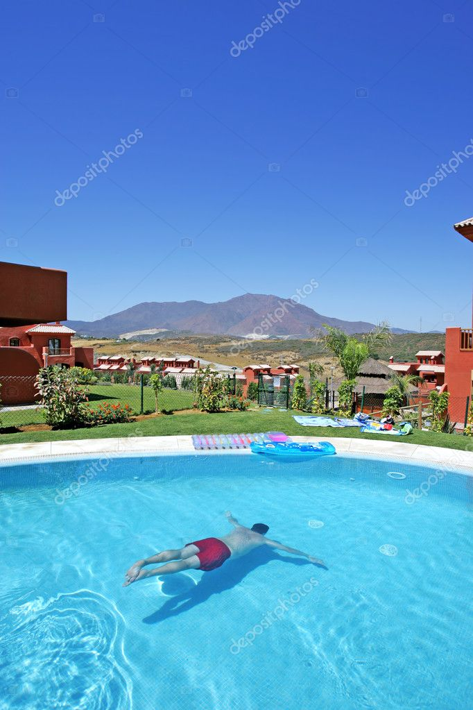 Man swimming underwater in sunny pool on sunny day in Spain whilst on vacation — Stock Photo #6232972