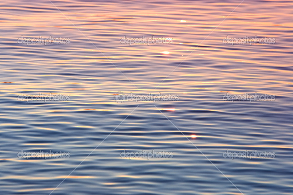 Early evening sun shimmering on calm water with an orange and pink glow  Stock Photo #6234544