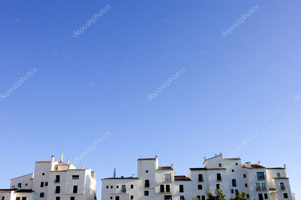 Sunny blue skyline of rows of white pueblo apartment blocks in Spain — Stock Photo #6234741