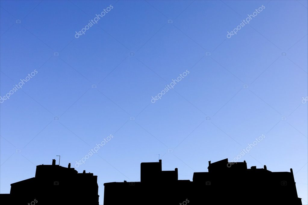 Silhouetted sunny blue skyline of rows of white pueblo apartment blocks in Spain — Stock Photo #6234743