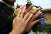 Wedding bouquet from frehs flowers and hands with rings — Stock Photo