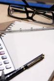 Pluma, libro, regla, calculadora y gafas — Foto de Stock