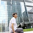 Businessman sitting on a bench in front of an office building — Stock Photo