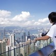 Royalty-Free Stock Photo: Tourist taking photo of Hong Kong skyline by his digital camera