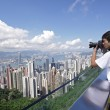 Stock Photo: Tourist taking photo of Hong Kong skyline by his digital camera