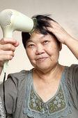 девушки, сушки ее волосы с сушилкой — Стоковое фото