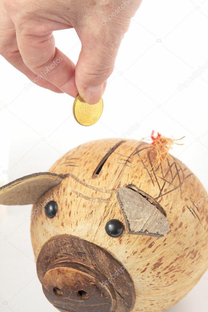 saving  male hand putting a coin into piggy bank   u2014 stock