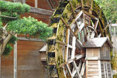Water wheel on old grist mill in forest — Stock Photo