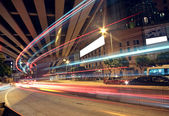Blurred bus light trails in downtown night-scape — Stock Photo